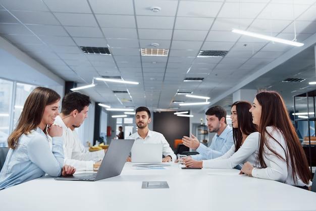 Freundliche atmosphäre. eine gruppe junger freiberufler im büro unterhält sich und lächelt