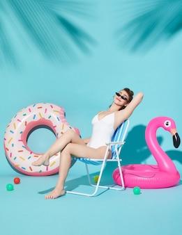 Freundliche attraktive frohe herrliche frauen kleideten in der netten badebekleidung an, die auf einem strandstuhl und einem gummiring sitzt
