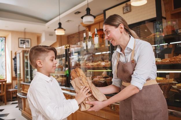 Freundliche bäckerin, die ihrem jungen kunden frisch gebackenes brot gibt