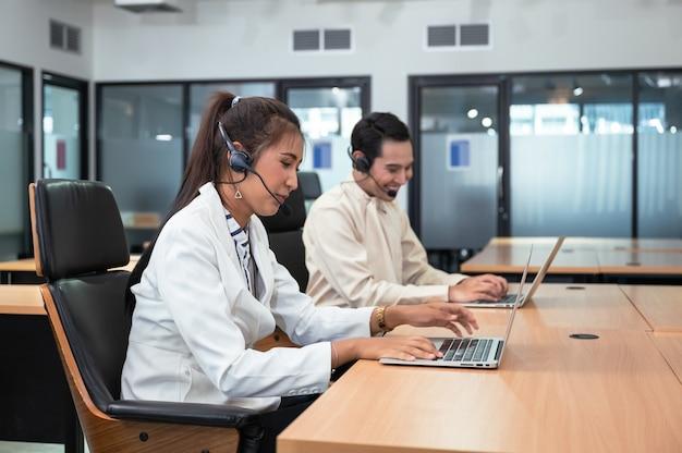 Freundliche betreiberin asiatische agentin mit headset, die mit laptop auf kundenberatung im büro mit kollege am arbeitsplatz arbeitet