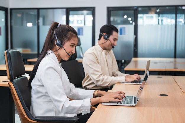 Freundliche betreiberin asiatische agentin mit headset, die mit laptop auf kundenberatung im büro mit kollege am arbeitsplatz arbeitet Premium Fotos
