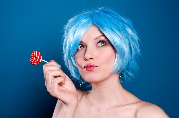 Freundliche bezaubernde frau in der blauen perücke mit einem lutscher in ihren händen