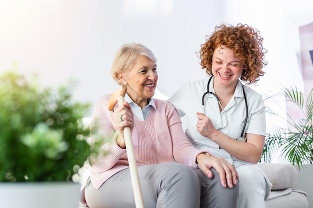 Freundliche beziehung zwischen lächelnder pflegekraft in uniform und glücklicher älterer frau. unterstützende junge krankenschwester, die ältere frau betrachtet.