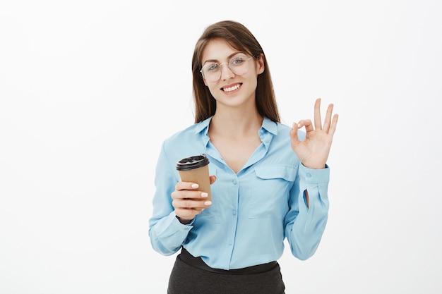Freundliche brünette geschäftsfrau, die im studio mit ihrem kaffee aufwirft