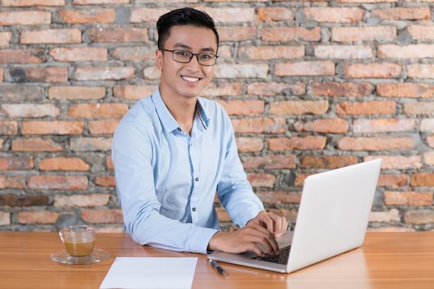 Freundliche business-mann arbeiten auf laptop am schreibtisch