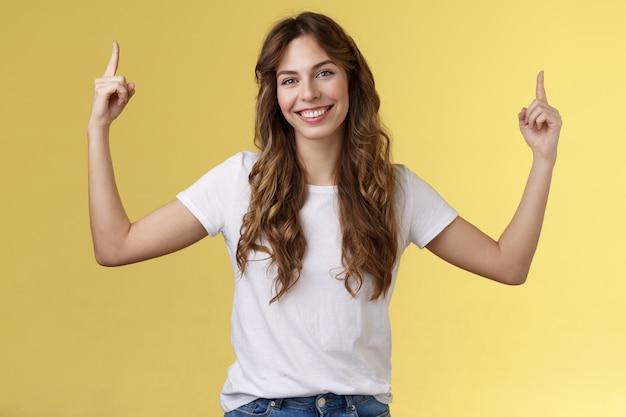 Freundliche, charismatische, gutaussehende frau, die ihnen einen großartigen promo-platz zeigt, der nach oben zeigt, zeigefinger hebt ...