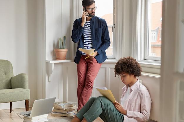 Freundliche erfolgreiche mitarbeiter sammeln informationen aus papieren