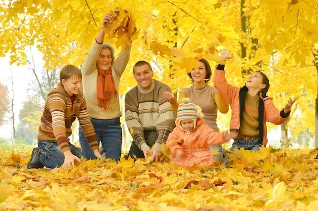 Freundliche familie auf einem spaziergang während des laubfalls im park