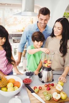 Freundliche familie, die fruchtsaft zubereitet