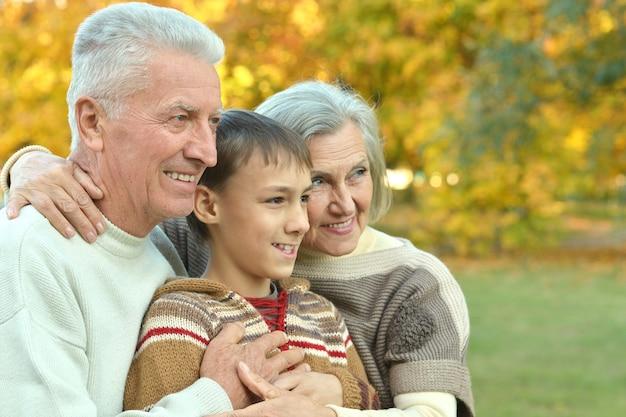 Freundliche familie, die im herbst im park spazieren geht