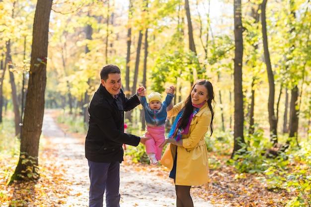 Freundliche familie, die im herbst zusammen im park spazieren geht