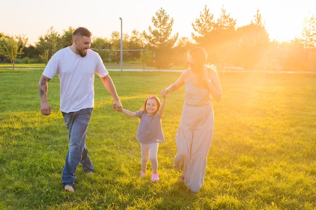 Freundliche familie, die im park spazieren geht und zusammen spaß hat.