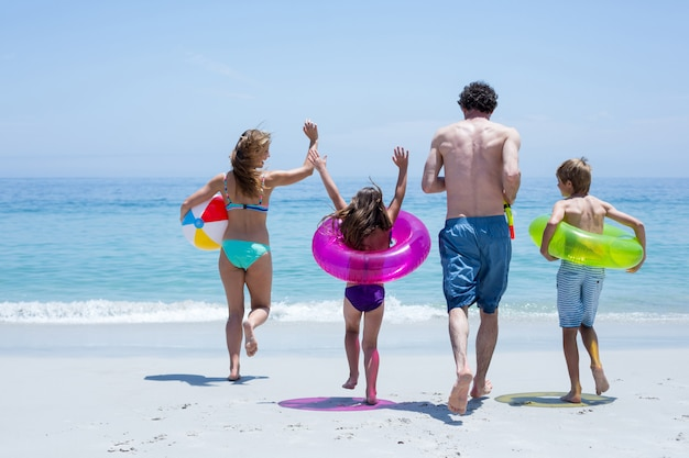 Freundliche familie, die in richtung zum meer mit schwimmenausrüstung läuft