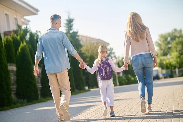 Freundliche familie. rückansicht eines schlanken, fröhlichen mannes, einer langhaarigen frau und eines kleinen mädchens mit rucksack, der an einem sonnigen tag händchen haltend auf der straße geht