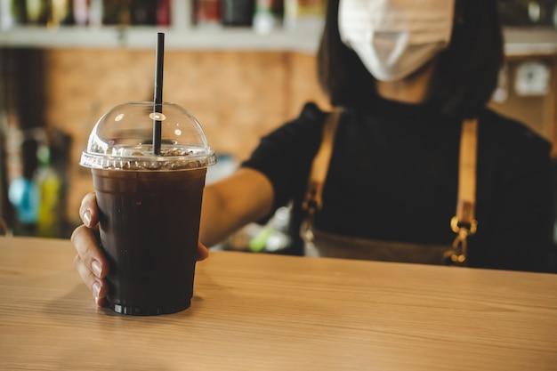 Freundliche frau barista trägt schutzgesichtsmaske und wartet auf das servieren von eisschwarzem kaffee an kunden im café-café, café-restaurant, service-geist, kleinunternehmer, essen- und getränkekonzept