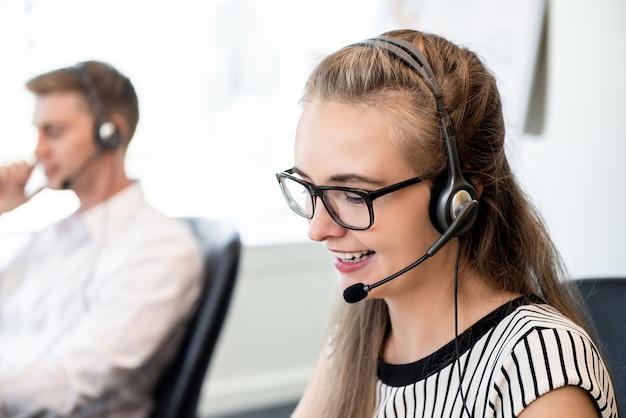 Freundliche frau, die im call-center-büro arbeitet