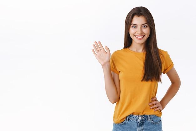 Freundliche fröhliche, glückliche lächelnde frau, die sie mit erhobener hand winkt. attraktives mädchen, das freund grüßt, hallo oder hallo sagen, willkommener gast, freudiger weißer hintergrund stehen, positivität und freude ausdrücken