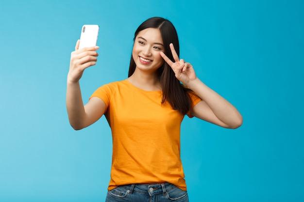 Freundliche, fröhliche, hübsche asiatische frau, brünett mit kurzem haarschnitt, die selfie macht, freudig lächelnd smartphone-show-frieden hält, victory-zeichen an der frontkamera des telefonbildschirms, familien-videoanruf spricht.