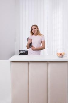 Freundliche gastgeberin an der rezeption des schönheitssalons bei der arbeit. lächelndes blondes mädchen mit notizbuch im weißen innenraum, freier raum