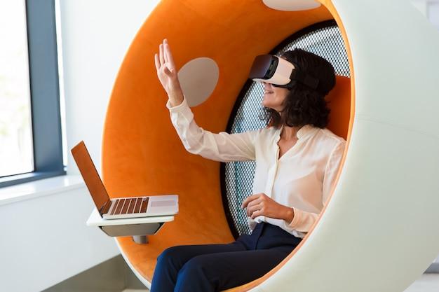 Freundliche geschäftsfrau mit laptop virtuelle darstellung aufpassend