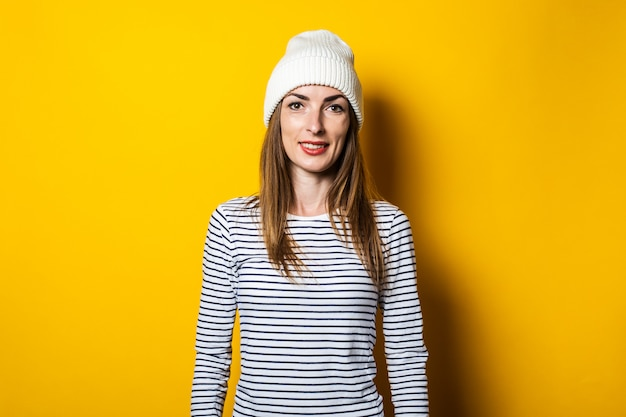 Freundliche glückliche junge frau in einem gestreiften pullover und hut auf gelbem hintergrund