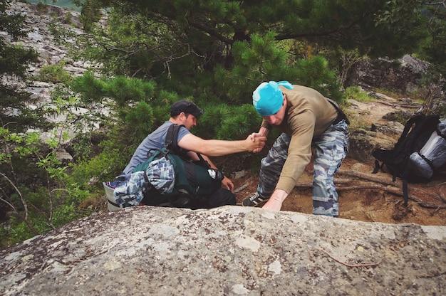 Freundliche hand auf der hochgebirgswanderung. männer helfen anderen wanderern, indem sie ihm die hand geben. wandern thema. berglehrer reichte jemandem eine helfende hand zum gipfel des berges.