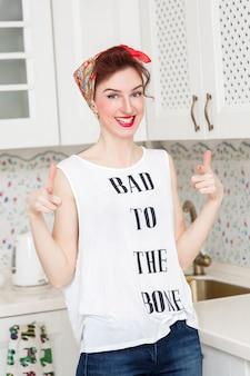 Freundliche hausfrau in einem roten halstuch in der küche