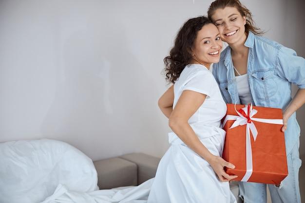 Freundliche internationale frau, die ein lächeln auf dem gesicht behält, während sie ein geschenk bekommt