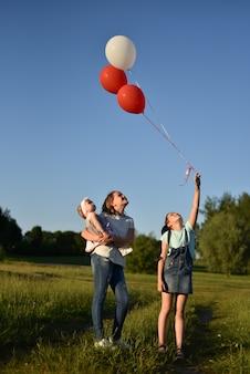 Freundliche junge familie mit den kindern, die im sommer in der natur stillstehen
