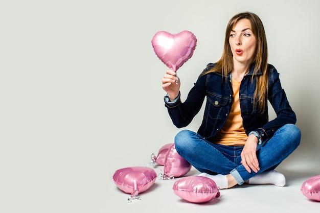 Freundliche junge frau, die mit gekreuzten beinen luftballons in der form eines herzens hält