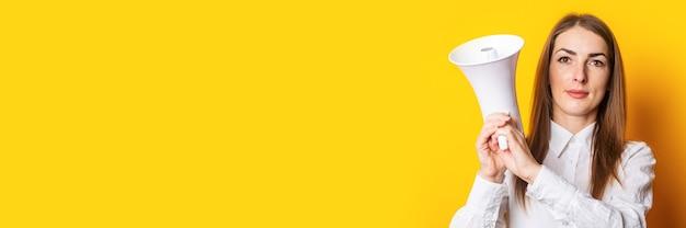 Freundliche junge frau hält ein megaphon in ihren händen auf einem gelben hintergrund