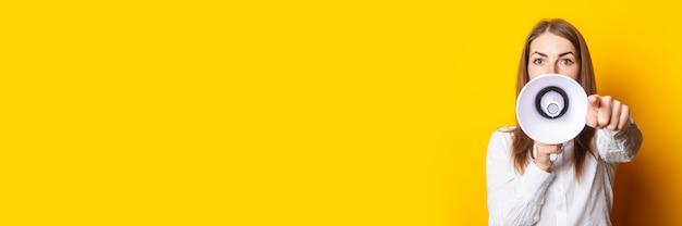 Freundliche junge frau hält ein megaphon in ihren händen und zeigt mit dem finger auf den betrachter auf gelbem grund