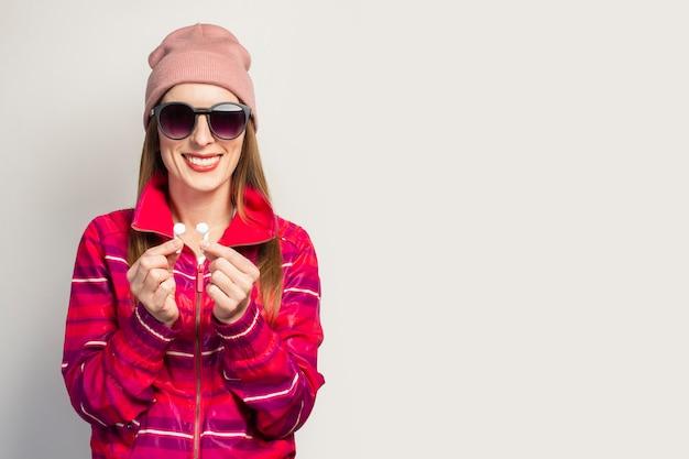 Freundliche junge frau in brille, hut und rosa sportjacke mit einem smiley hält drahtlose kopfhörer