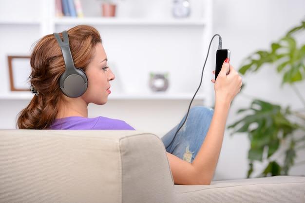 Freundliche junge frau in den kopfhörern hörend musik