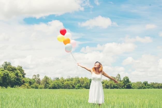Freundliche junge frau mit ballons an einem sonnigen tag spielen