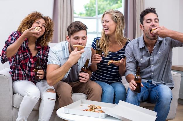 Freundliche junge freunde, die pizza genießen