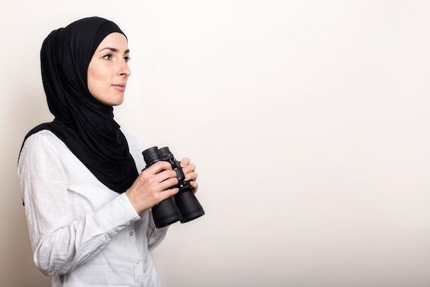 Freundliche junge muslimische frau im weißen hemd und im hijab hält fernglas
