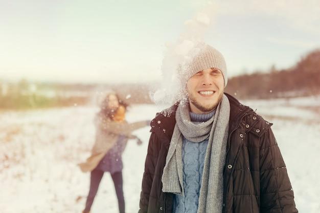 Freundliche junge paare, die schneebälle spielen