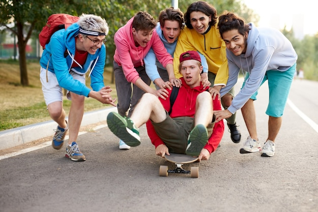 Freundliche jungs reiten ihren kerl auf skateboard