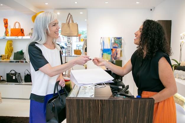 Freundliche kassiererin, die dem kunden nach der zahlung eine kreditkarte gibt, sich für den kauf bedankt und lächelt. mittlerer schuss. einkaufskonzept