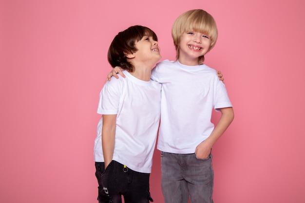 Freundliche kinder, die niedliches entzückendes lächeln auf rosa schreibtisch umarmen
