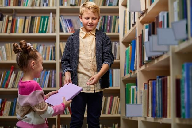 Freundliche kinder, die sich gegenseitig bücher geben, vor der schule in der bibliothek helfen und lächeln