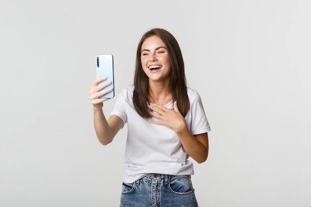 Freundliche lächelnde frau videoanruf und sprechen auf smartphone glücklich, weiß stehend.