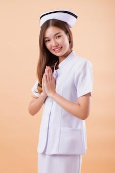 Freundliche lächelnde krankenschwester, die asiatische thailändische begrüßungsgeste tut