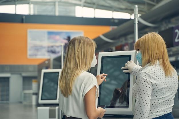 Freundliche, langhaarige blonde frau, die eine medizinische maske trägt, während sie dem sicherheitspersonal zuhört?
