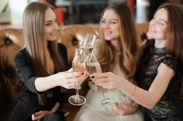 Freundliche mädchen, die gläser champagner an der party klirren