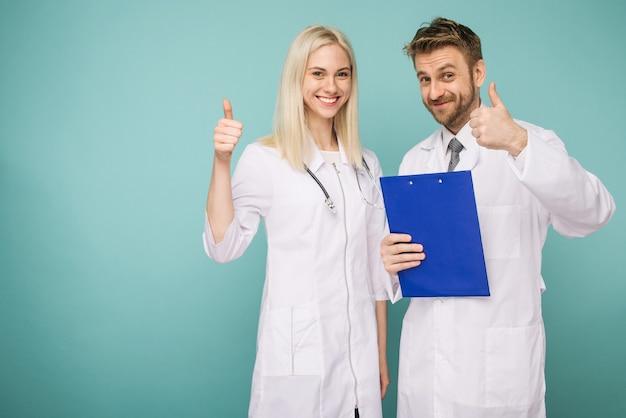 Freundliche männliche und weibliche ärzte. glückliches medizinisches ärzteteam. daumen hoch