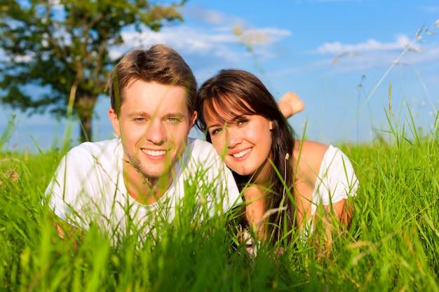 Freundliche paare, die im grünen gras in einer sonnenbeschienen wiese liegen