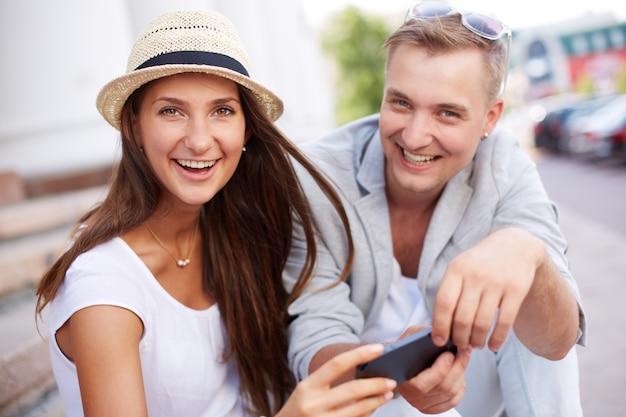 Freundliche paare, die spaß mit dem smartphone spielen