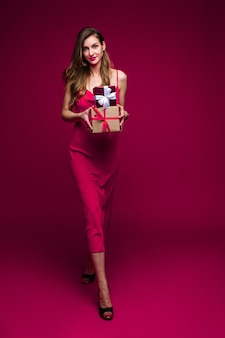 Freundliche passende junge frau mit geschenken, die festliches abendkleid tragen, das auf rosa studiohintergrund mit kopienraum für anzeige aufwirft